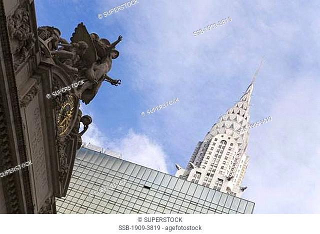 Grand Central Station Clock skyscraper and Chrysler Building in sun sunshine with blue sky in midtown Manhattan New York USA