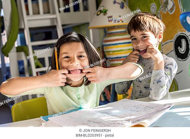 Hispanic children making faces together