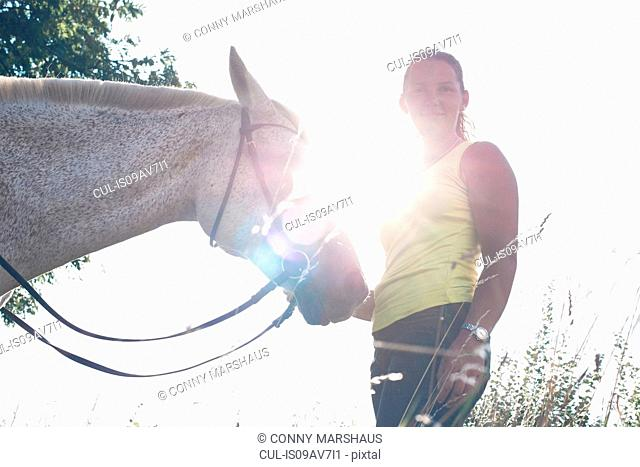 Portrait of woman with grey horse against sunlit sky
