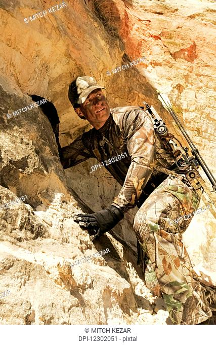 Extreme Bowhunting Hunter Climbing On Rocks With Bow On Back
