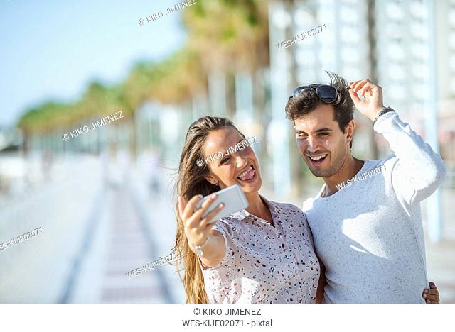 Happy young couple taking a selfie on promenade