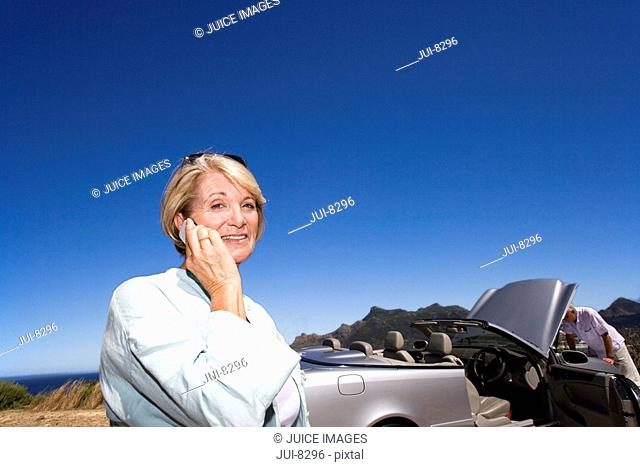 Senior woman using mobile phone outdoors, smiling, portrait, man looking in engine of convertible silver car in background