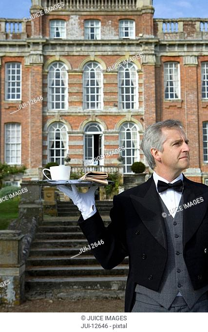 Mature butler with tray of tea by manor house