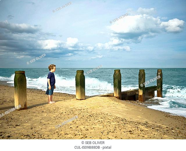 Boy standing on beach looking out at sea, Southwold, Sussex, UK