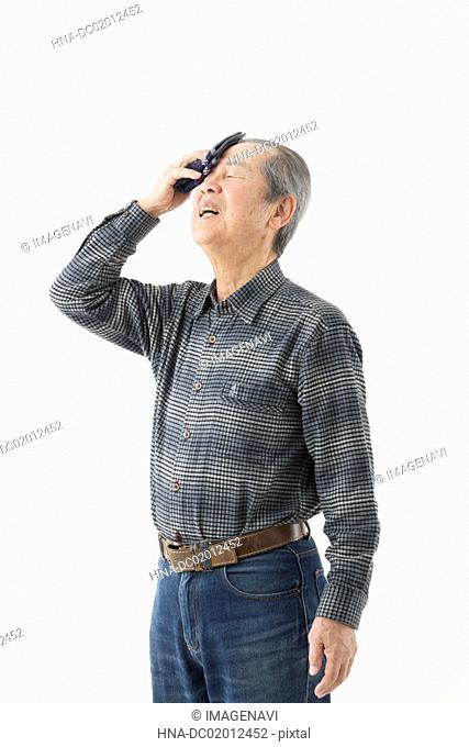Senior man wiping off sweat