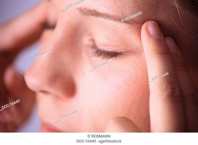 Young woman makes a hand reflexology massage - massages her left forefinger