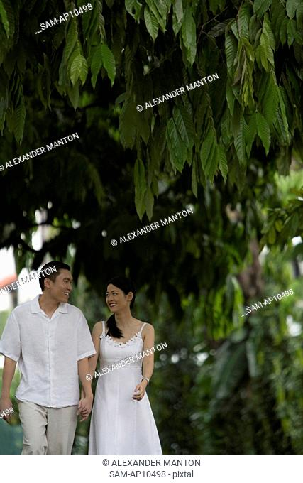 Singapore, Man and woman holding hands and smiling at each other