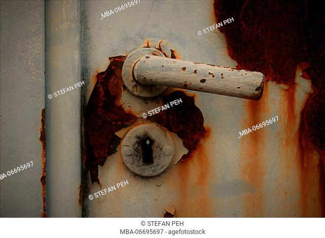 Rusted door lock of a court driveway with cracked grey varnish and rust