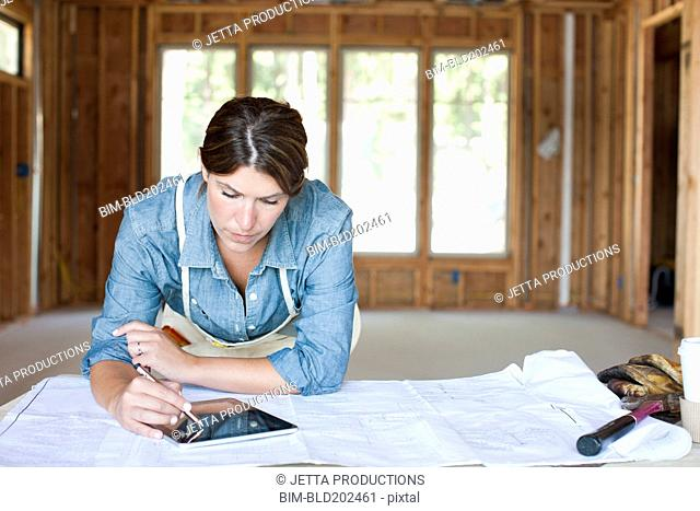 Caucasian construction worker using digital tablet in unfinished room