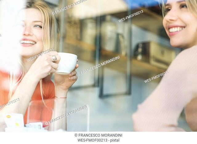 Two smiling young women in a cafe looking out of window