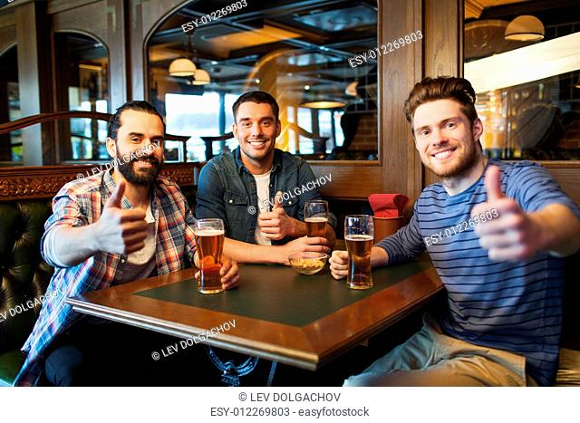 people, leisure, friendship and and bachelor party concept - happy male friends drinking beer and showing thumbs up at bar or pub