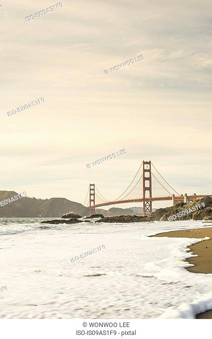 View of Golden Gate Bridge and beach waves, San Francisco, California, USA