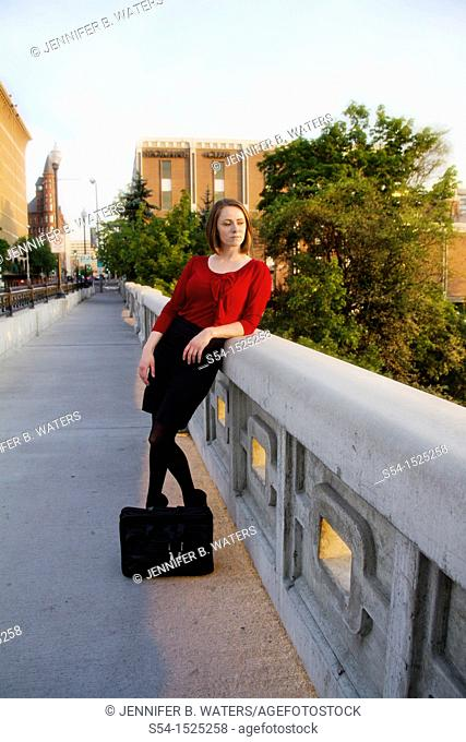 Young businesswoman of Russian descent in Spokane, Washington, USA, standing on the Monroe Street Bridge in downtown