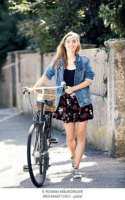 Young woan with bicycle in the city