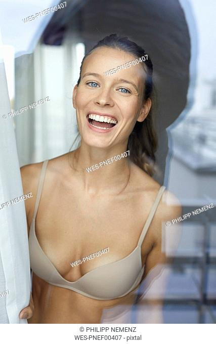Portrait of laughing young woman behind windowpane wearing bra