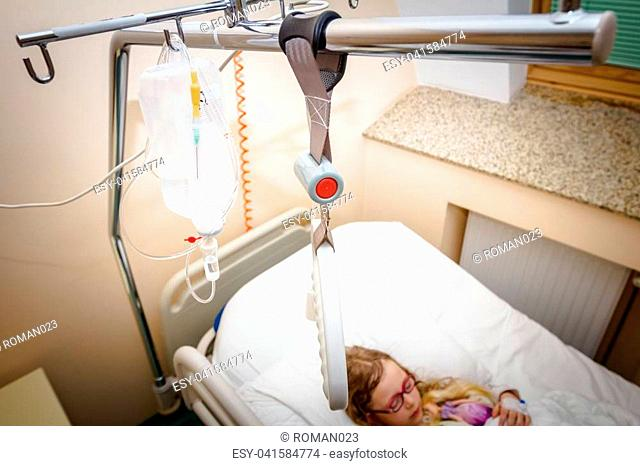 Above hospital bed is hanging adaptive triangular metal frame and bag of infusion