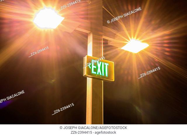 Bright lights above a lighted exit sign at night