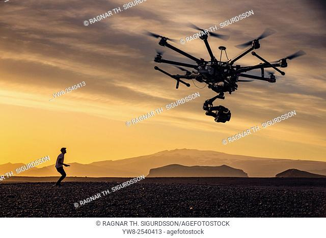 Man flying a radio controlled drone with a camera at sunset in the Central Highlands, Iceland