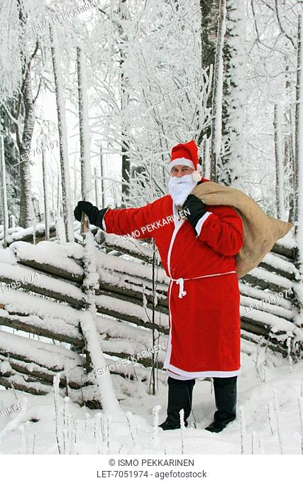 Santa Claus standing with a gift sack on his back next to a snowy rail fence