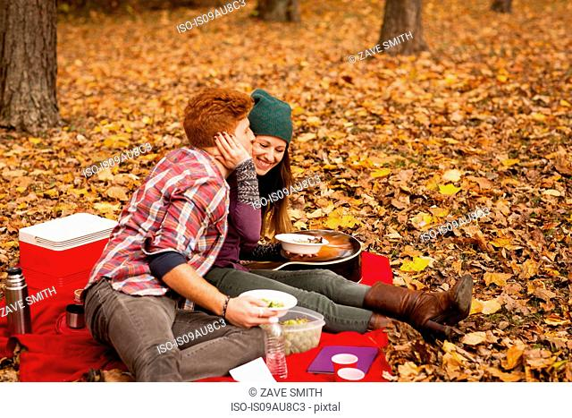 Romantic young couple having picnic in autumn forest