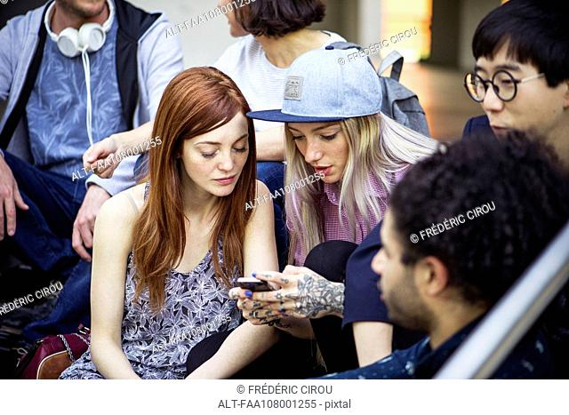 Young adult friends hanging out and using smartphone together