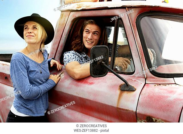 Smiling young couple with an old pick up