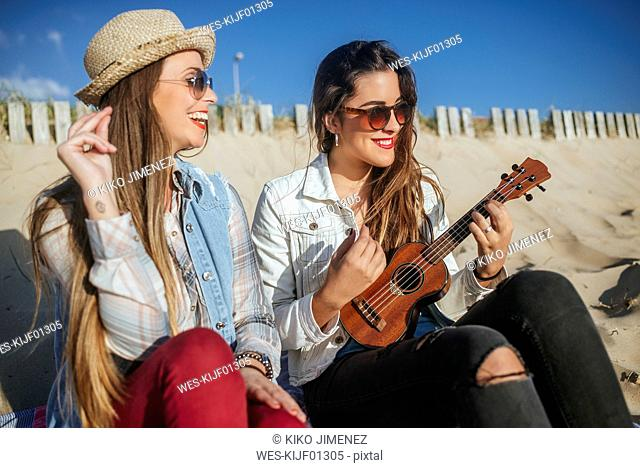 Two young women with ukulele sitting on the beach