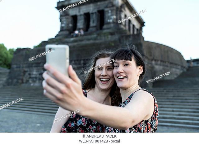 Germany, Koblenz, Deutsches Eck, tourists taking selfie at Emperor-Wilhelm monument