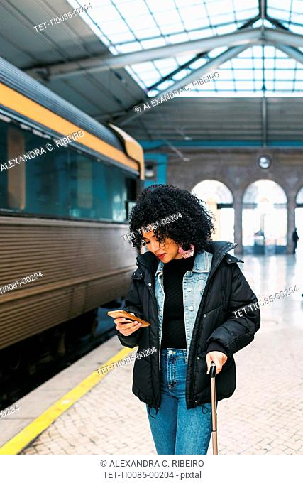 Young woman using smart phone in railway station