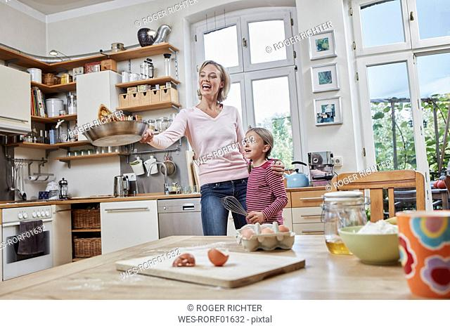 Happy mother and daughter baking pancakes in kitchen at home together