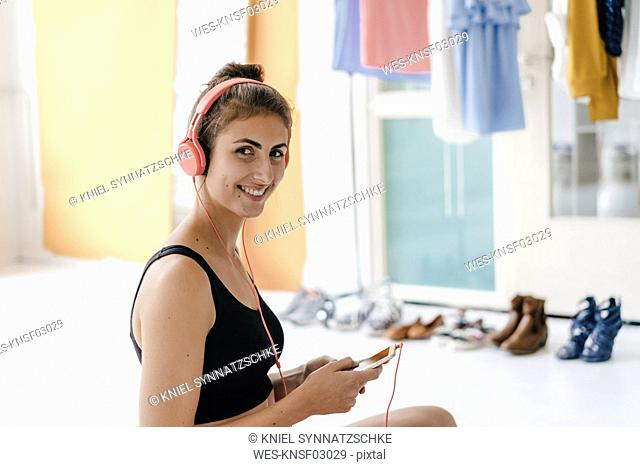 Smiling young woman in sportswear listening to music