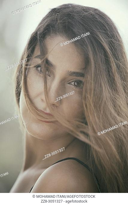 Beautiful young woman hair covering face