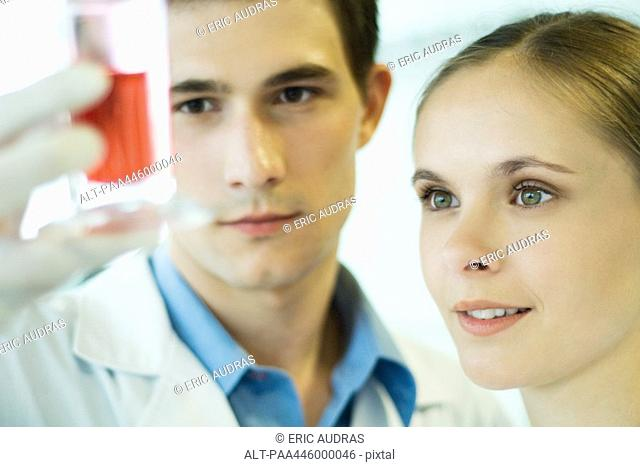 Young male and female lab workers, holding up test tube
