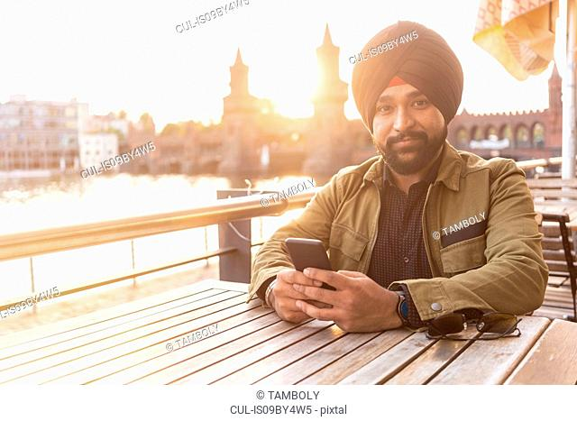 Indian man using smartphone in cafe by river, Berlin, Germany