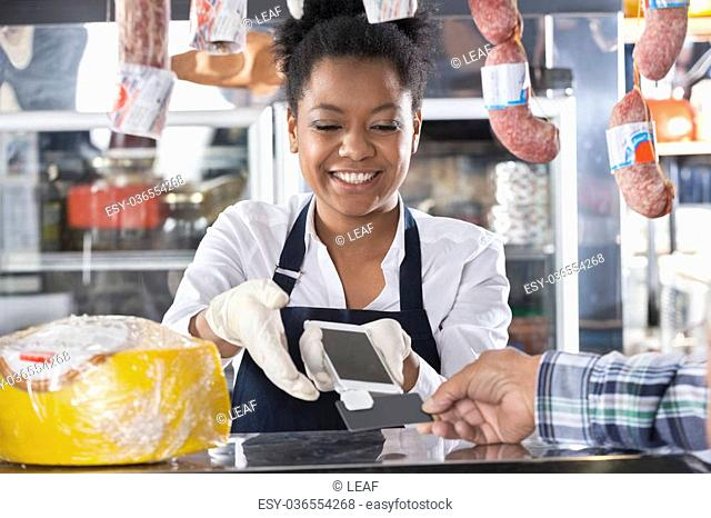 Happy saleswoman accepting credit card payment from customer in cheese shop