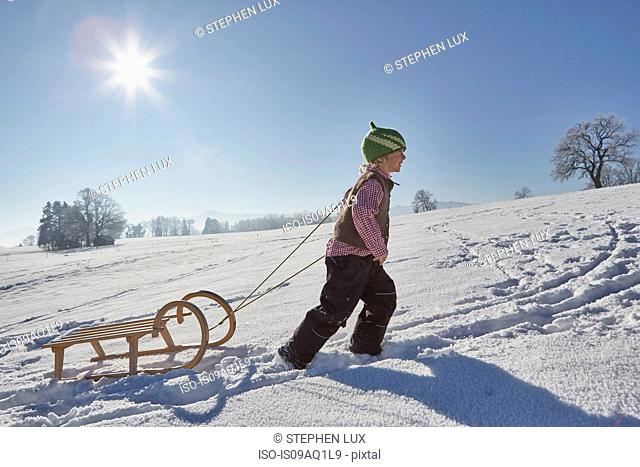 Young boy pulling sled uphill