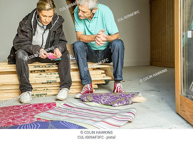 Senior couple making decision on wallpaper