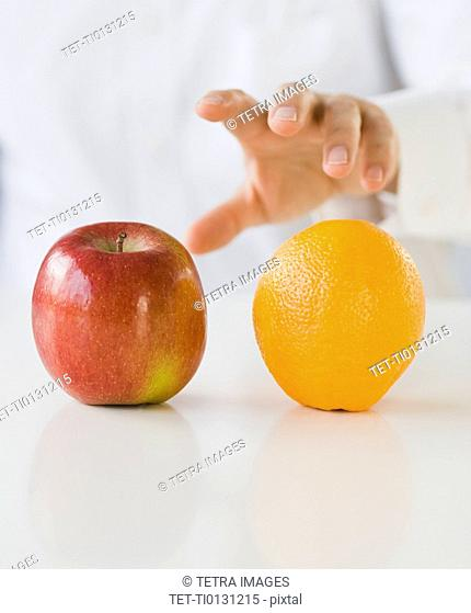 Man reaching for apple and orange