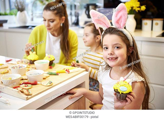 Portrait of smiling girl showing Easter cupcake in kitchen