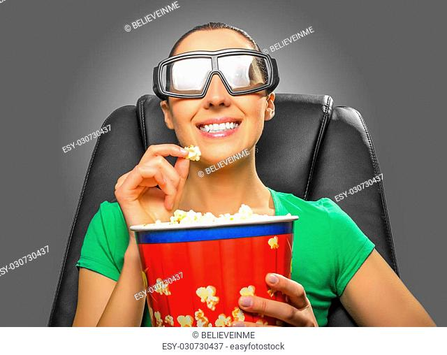 Viewer watching 3D cinema in spectacles with bowl full of popcorn