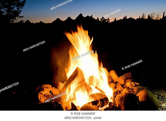 A Campfire In Front Of The Grand Teton Mountains In Jackson Hole, Wyoming