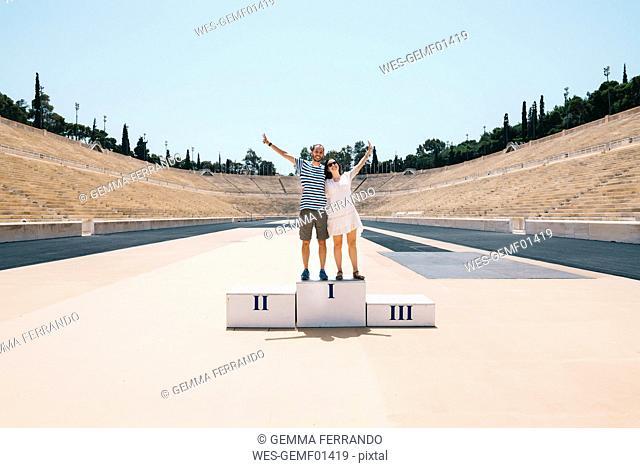 Greece, Athens, couple on the podium celebrating in the Panathenaic Stadium