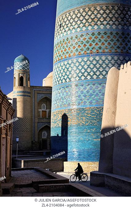Silhouette of a man on a bicycle in front of the unfinished minaret Kalta Minor. Uzbekistan, Khorezm, Khiva, Itchan Kala (inner town)
