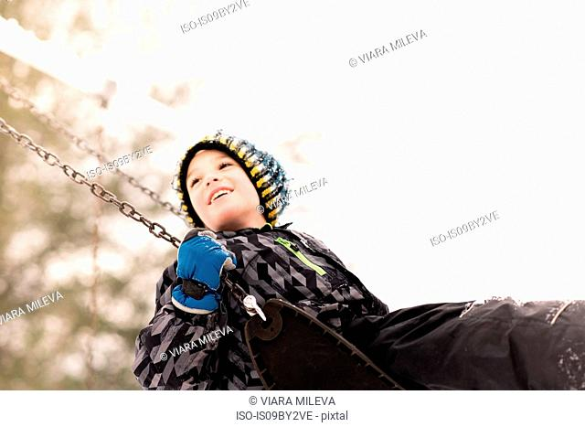 Boy in knit hat swinging on playground swing in winter