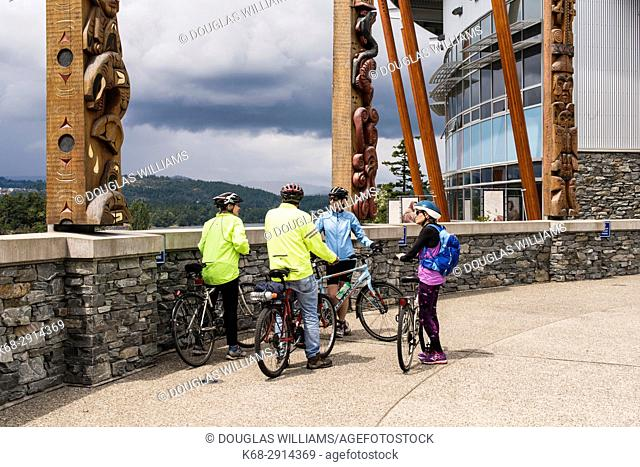 Group of four bicyclists in front of the Songhees Wellness Centre, Victoria, BC, Canada