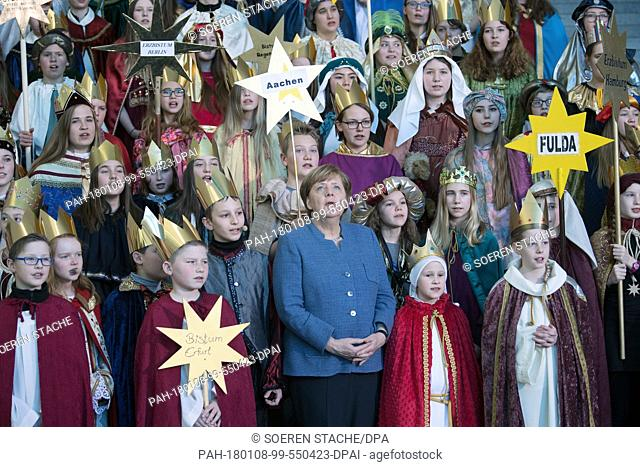 German chancellor Angela Merkel of the Christian Democratic Union sings with the boys and girls during the traditional welcoming of the carol singers in Berlin