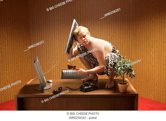 Businessman dressed as caveman crouching on desk