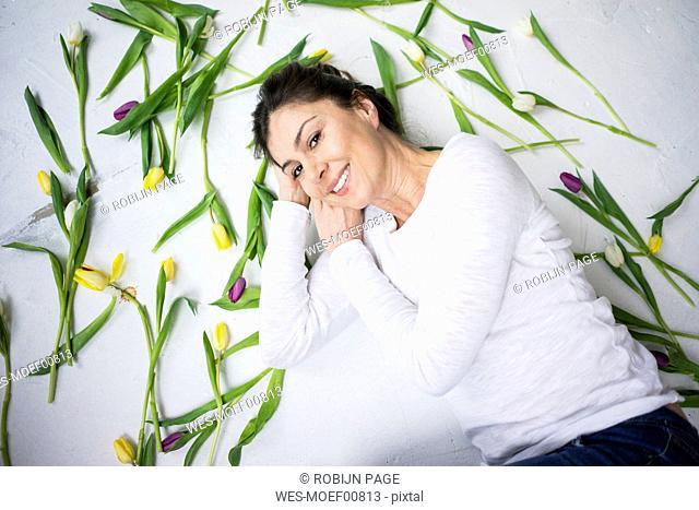 Smiling woman lying on floor amidst tulips