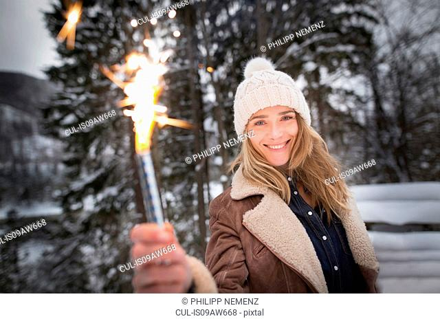 Woman holding smoke flare in winter