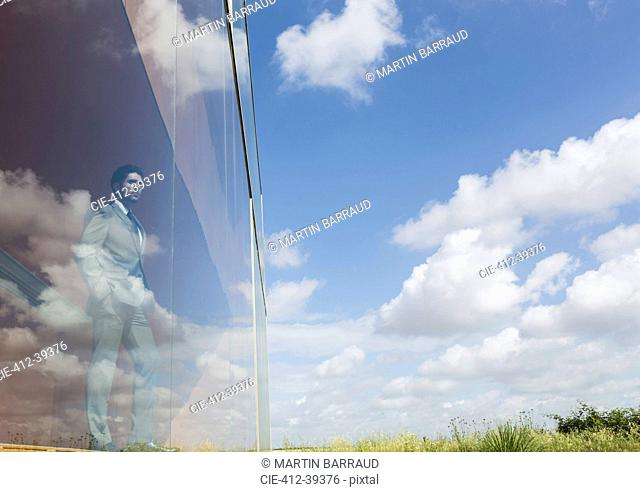 Pensive businessman looking out modern office window at sunny blue sky and clouds